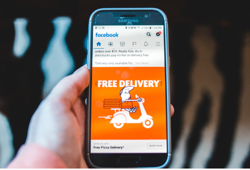 Person holding phone with a Facebook Ad displayed
